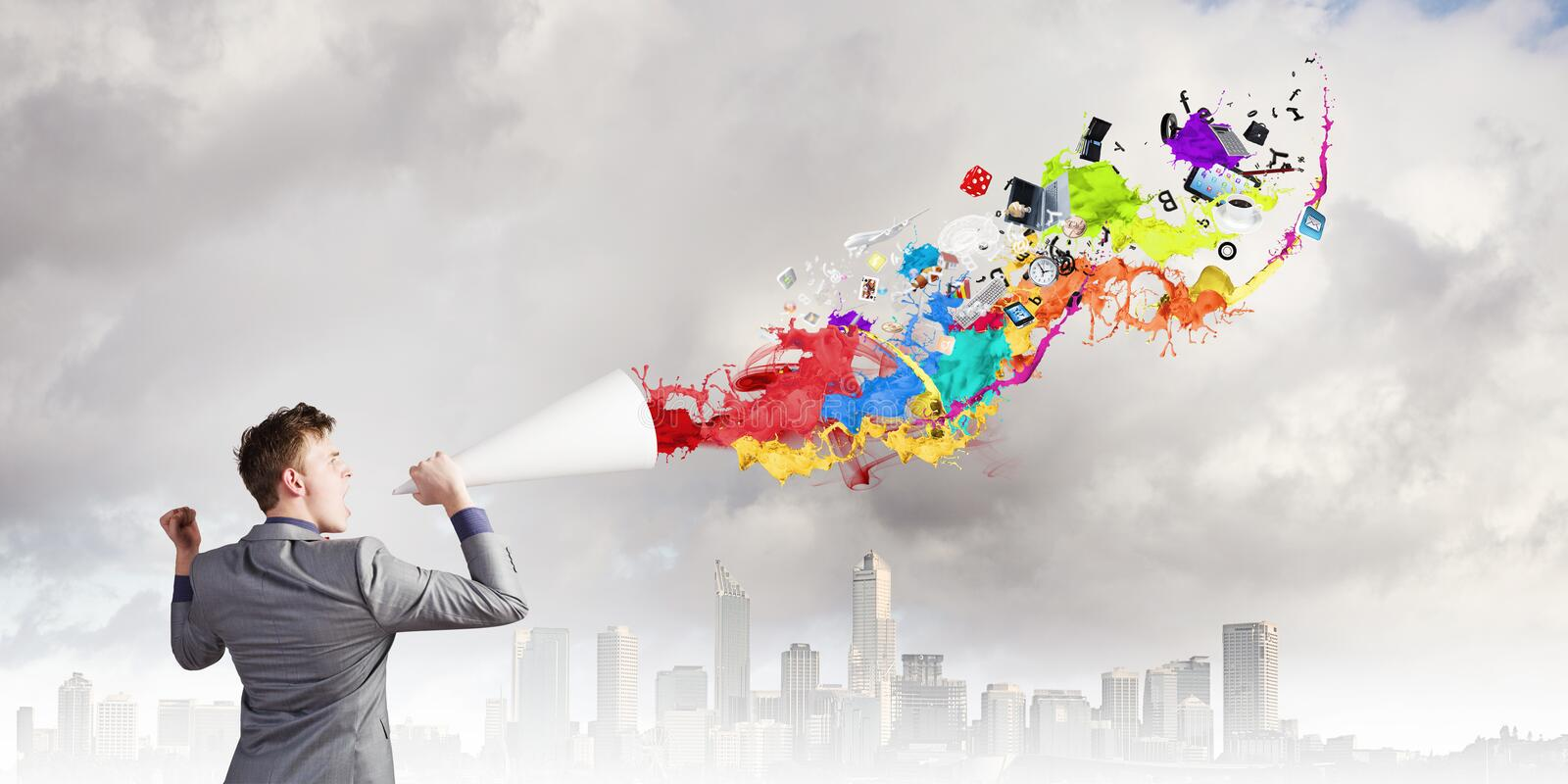 Man with bullhorn. Young businessman speaking in trumpet and colorful splashes flying out stock images