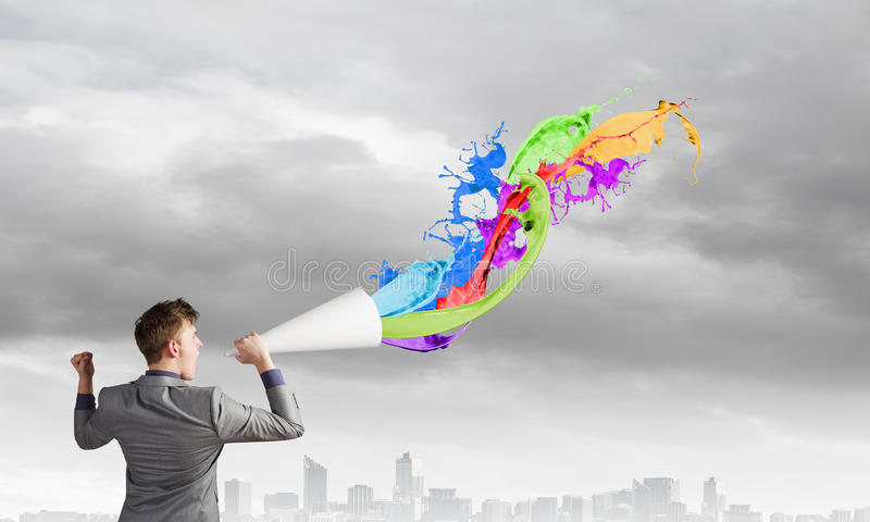 Man with bullhorn. Young businessman speaking in trumpet and colorful splashes flying out stock image