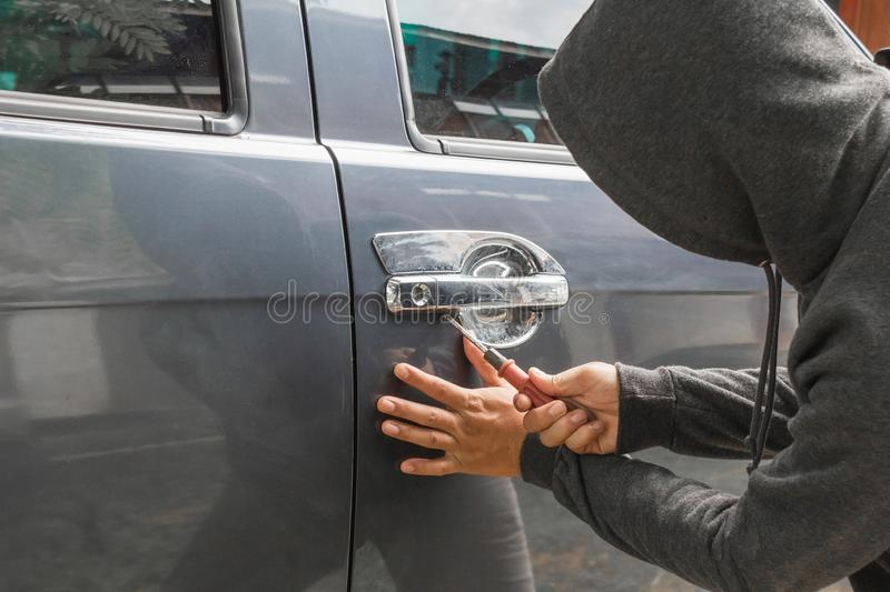 Man burglar stealing car stock photography