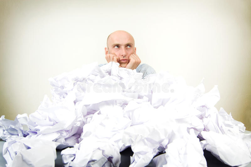 Man buried in pile of work. Bald headed middle aged businessman buried in pile of paperwork; studio background royalty free stock image