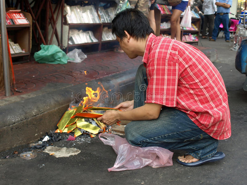 Man Burning Ghost Money During Chinese New Year stock photo