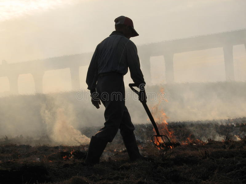 A man burns his fields in Taiwan. A man with a hat burns and chars his smoky fields on an island in Asia stock photo