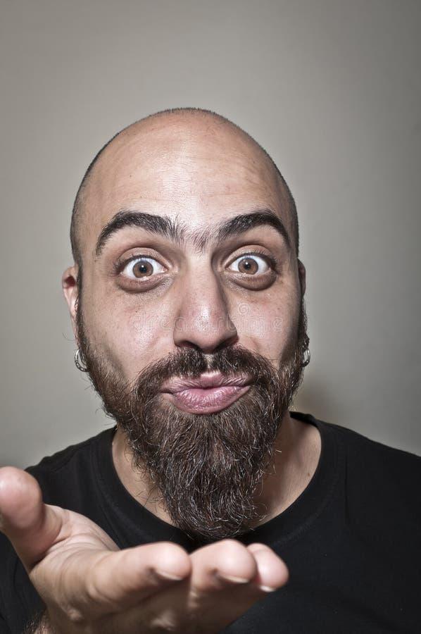 Man with a bushy beard that blows a kiss