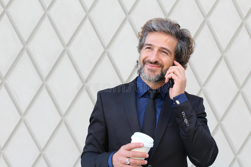Man in business clothes holding coffee cup and smartphone royalty free stock images