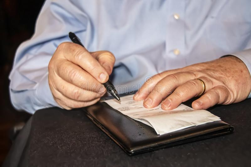 Man in business shirt with wedding ring signs credit card bill at restaurant - close-up of hands and check on black tablecloth - royalty free stock photos