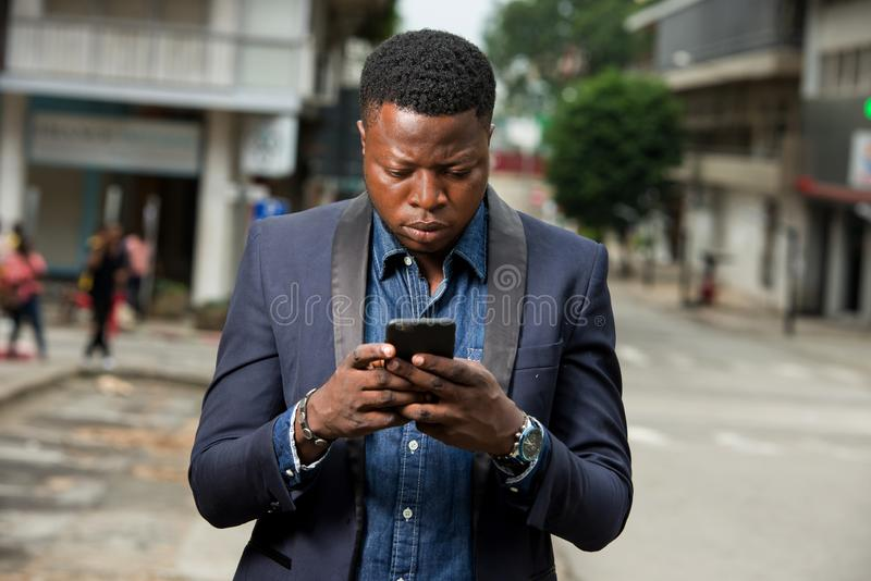 Man in business suit is enjoying modern mobile technologies. In city.Concept of modern technologies order by phone stock photography