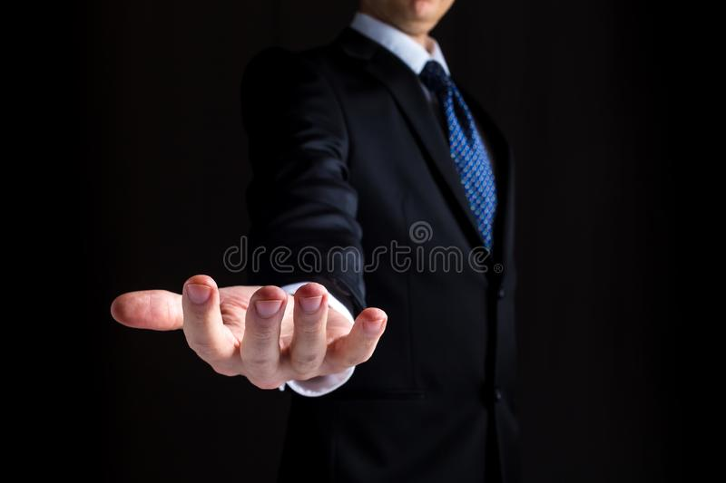 Man holding his hand out and showing something. Man in a business suit holding his hand out and showing something stock photo