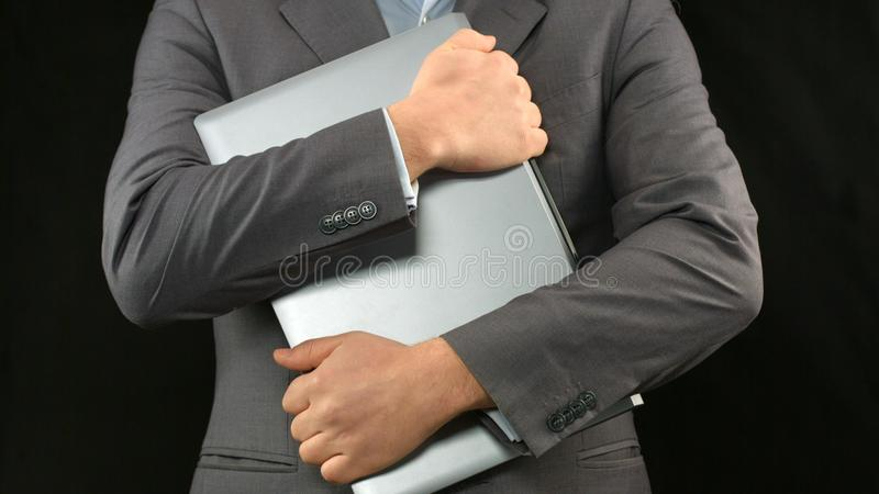 Man in business suit holding laptop computer tight, personal data security royalty free stock photography