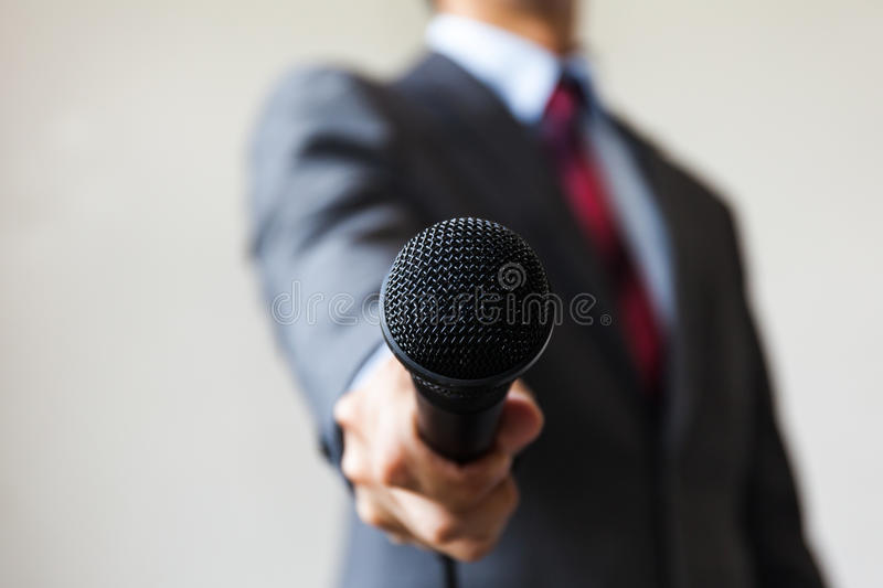 Man in business suit holding a microphone conducting a business. Interview, journalist reporting, public speaking, press conference, MC royalty free stock image