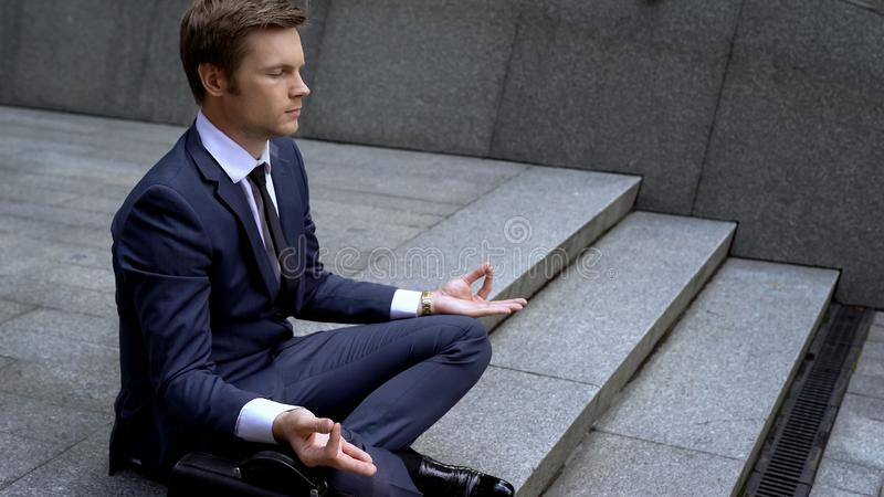 Man in business suit sitting in lotus position, gaining self-control in business. Stock photo stock photos