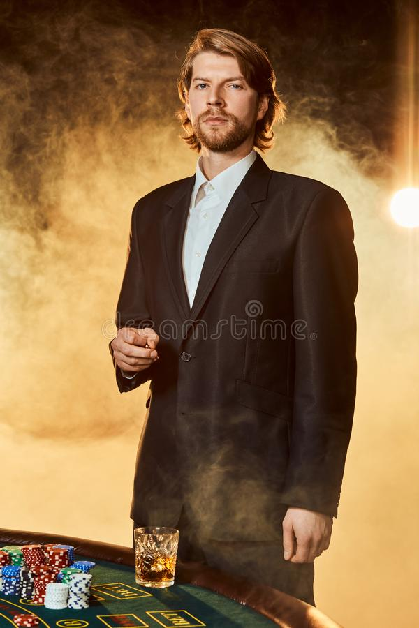 A man in a business suit standing near the game table. Male player. Passion, cards, chips, alcohol, dice, gambling royalty free stock photo