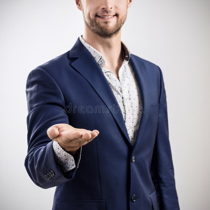 Man shows outstretched hand with open palm. Man in business suit standing and shows outstretched hand with open palm royalty free stock image