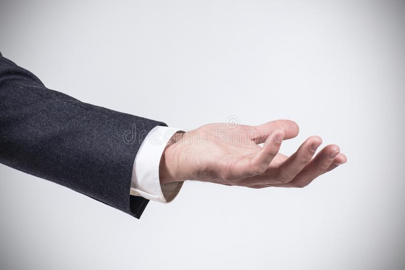 Man in suit shows outstretched hand with open palm. Man in business suit standing and shows outstretched hand with open palm royalty free stock images
