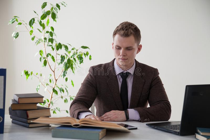 A man in a business suit works at the computer with books in the Office royalty free stock photography