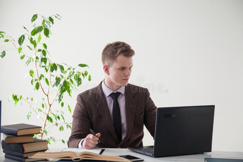 A man in a business suit works at a desk with a computer and books in the Office royalty free stock photography