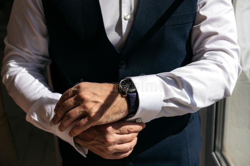 A man in a business suit zips up shirt cuffs royalty free stock photography