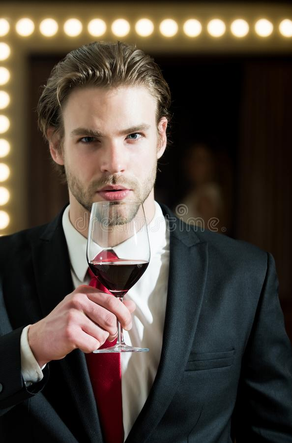 Man or businessman hold wine glass, meeting and relax. Man or businessman with beard and hairstyle in formal outfit with red tie hold wine glass near woman in stock photos