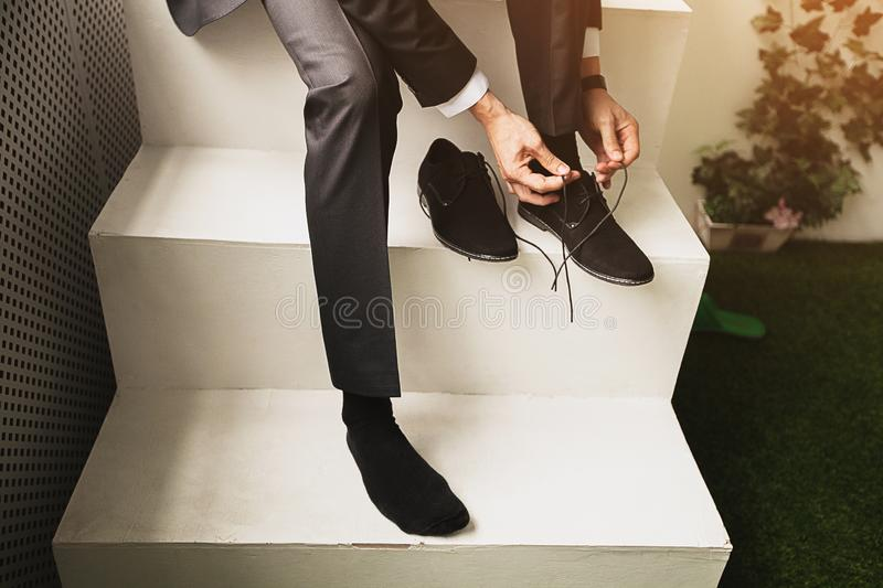 The man, a businessman, an entrepreneur or the groom sits on a white ladder and a new tying shoelace black suede shoes business, royalty free stock photos