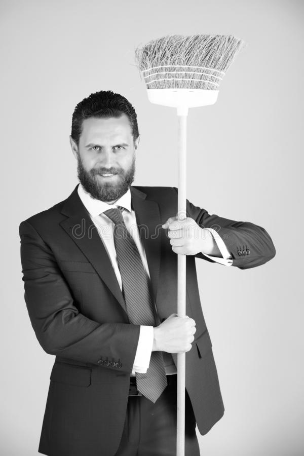 Man or businessman with happy face, broom in business outfit royalty free stock image