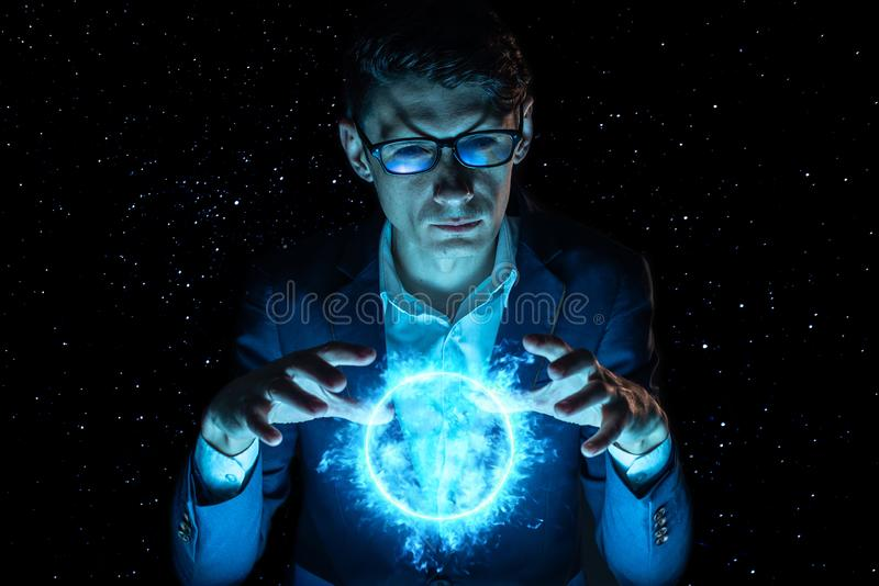 Man businessman holding hands over a blue glowing plasma sphere. Magic prediction and foresight in business and Finance royalty free stock photos