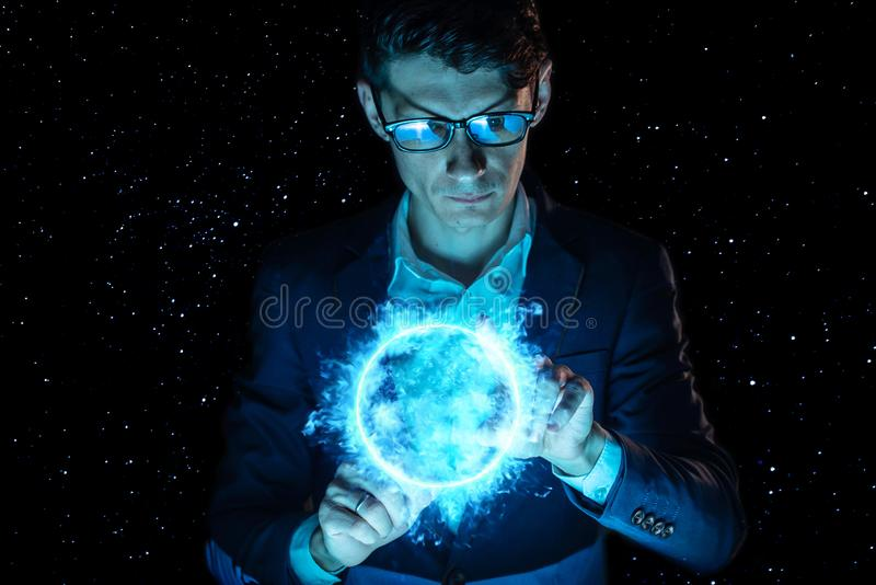 Man businessman holding hands over a blue glowing plasma sphere. Magic prediction and foresight in business and Finance. A man businessman holding hands over a royalty free stock images