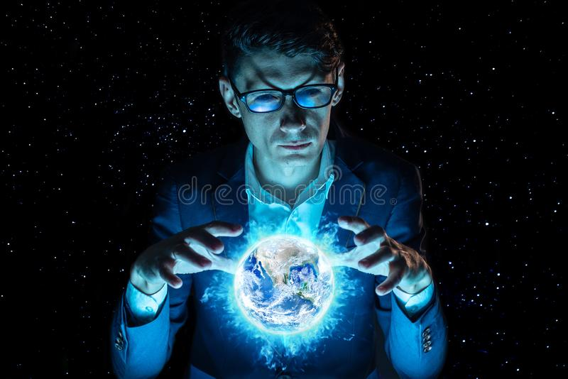 Man businessman holding hands over a blue glowing sphere in the form of planet earth. Elements furnished by NASA royalty free stock image