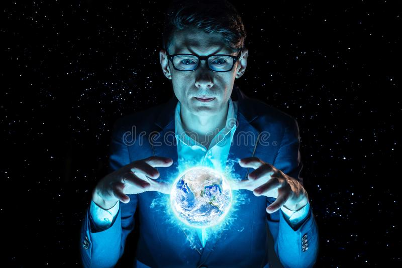 Man businessman holding hands over a blue glowing sphere in the form of planet earth. Elements furnished by NASA stock photography