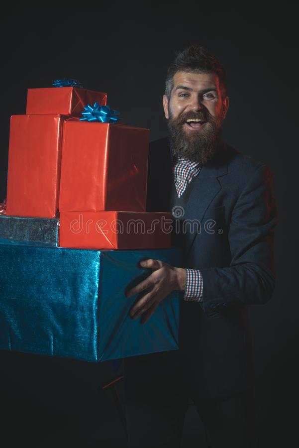 Man or businessman holds pile of gifts on black background. Hipster with beard and mustache in suit holds boxes and presents. Gifts and presents concept. Man stock photography