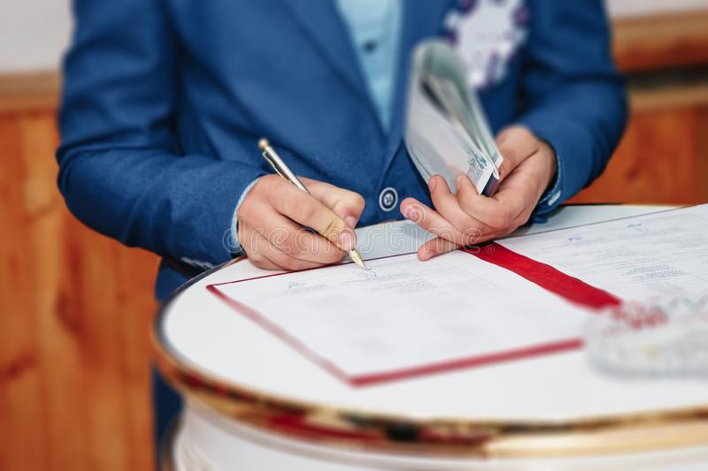 Man businessman signs documents with a pen making the signature sitting at the desk in the light. With retro effect.  royalty free stock photos