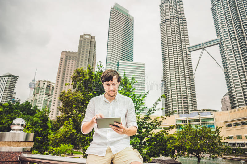 Man businessman or student in casual dress using tablet a tropical park on the background of skyscrapers. Dressing in a white shir stock photography