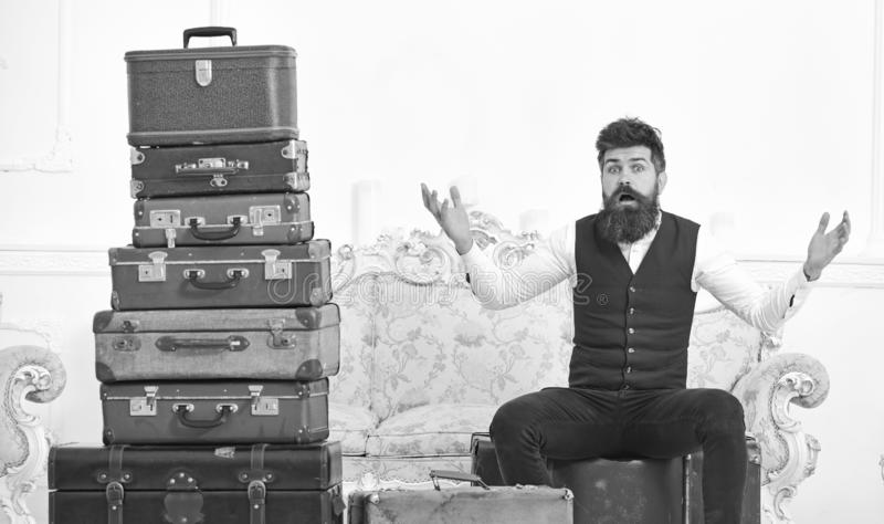 Man, butler with beard and mustache delivers luggage, luxury white interior background. Macho elegant on surprised face. Sits shocked near pile of vintage stock photos
