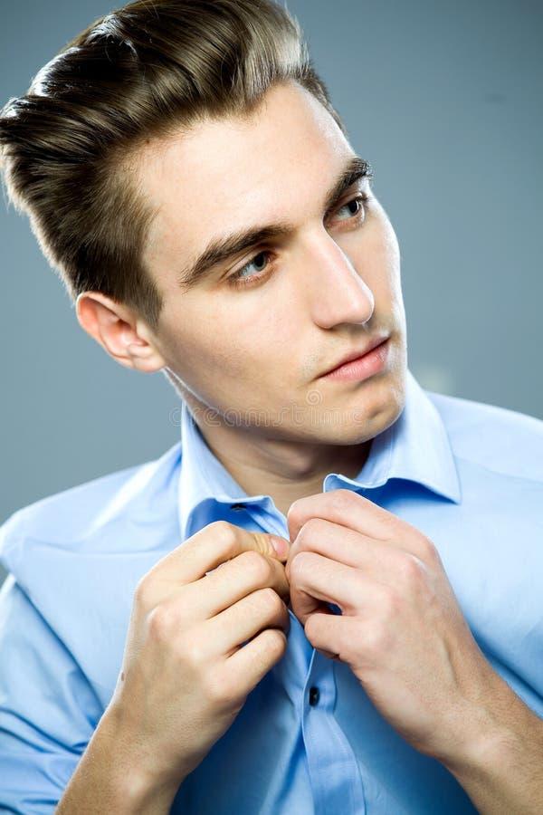 Man buttoning shirt