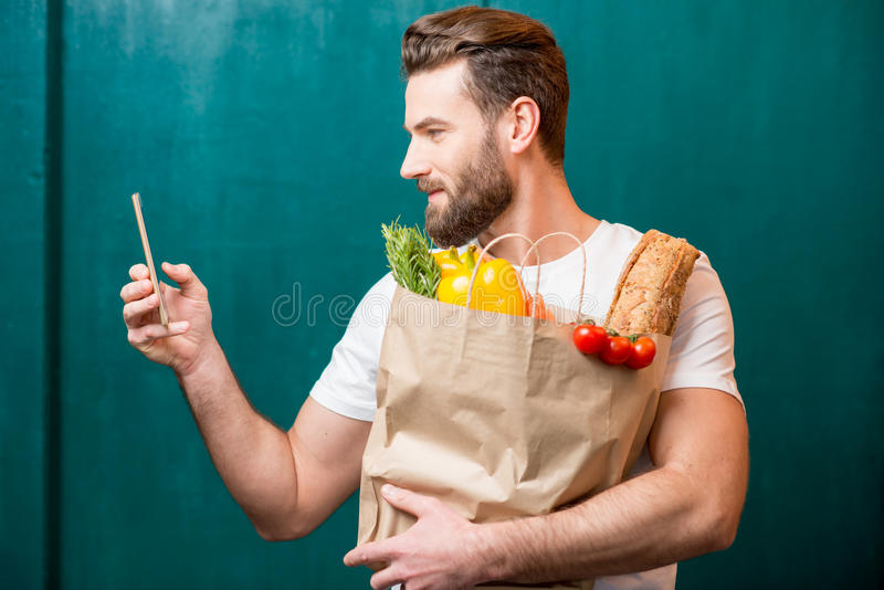 Man buying food online. Man making online purchase with smart phone holding paper bag full of healthy food on the green background stock image
