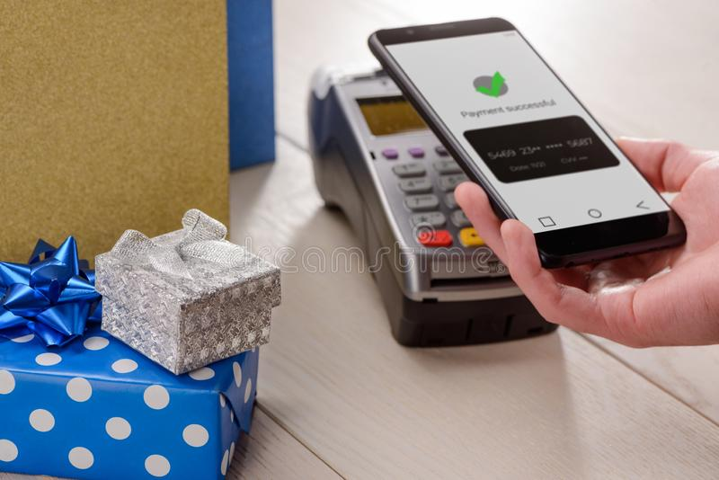 Man buying holiday gifts. And paying with his phone successfuly. Contactless payment with e-money stock images