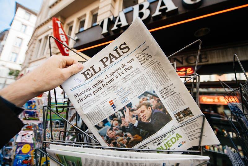 Man buying international press with Emmanuel Macron and Marine l. PARIS, FRANCE - APRIL 24: Man buy looks at press kiosk at Spanish El Pais newspaper with royalty free stock photos
