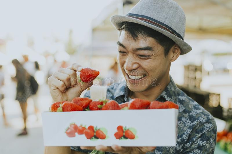 Man buying strawberries at a farmers market royalty free stock photo