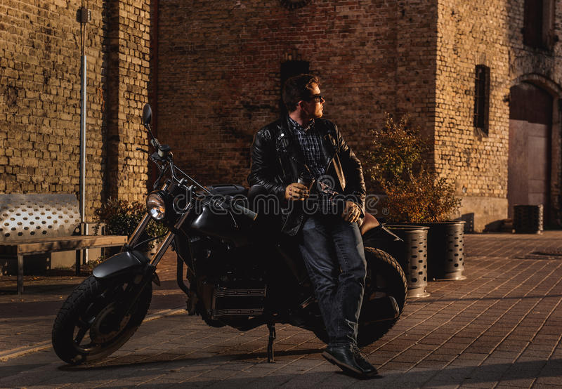 Man with a cafe-racer motorcycle. Outdoors royalty free stock photo