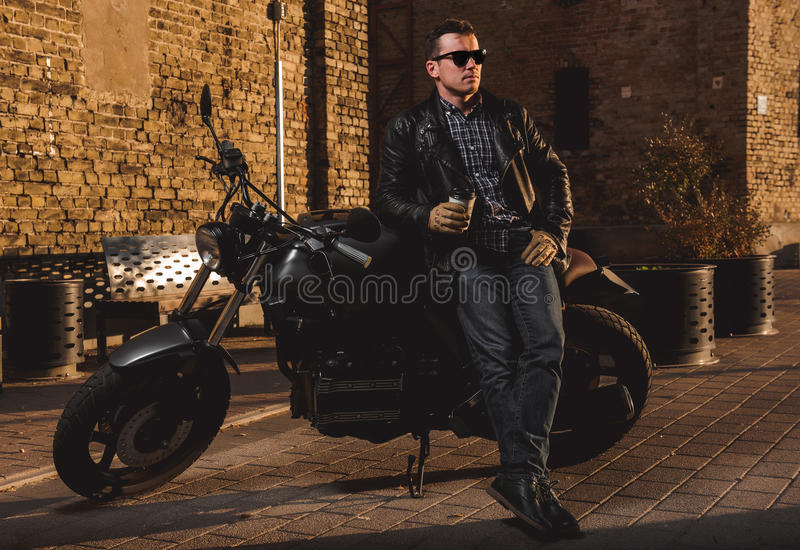 Man with a cafe-racer motorcycle. Outdoors royalty free stock image