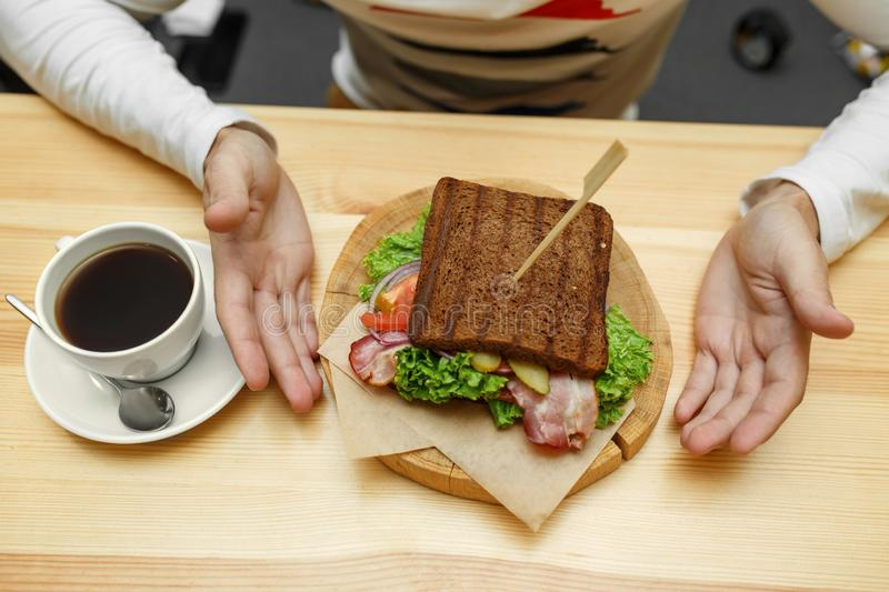 Man in cafe take his order sandwich and coffee royalty free stock images