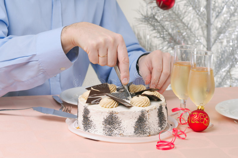 Man with cake. Man cutting Cake against Christmas tree royalty free stock images