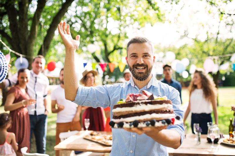 Man with a cake on a family celebration or a garden party outside. stock photo