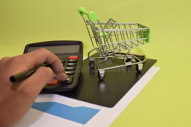 Man calculate budget cost and analysis financial. Selective focus on shopping cart. Business and finance concept of office desk stock photo