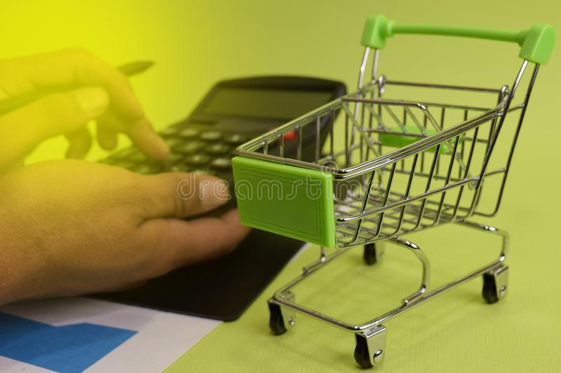 Man calculate budget cost and analysis financial. Selective focus on shopping cart. Business and finance concept of office desk stock photos