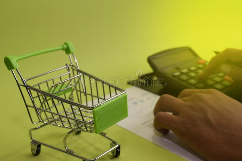 Man calculate budget cost and analysis financial. Selective focus on shopping cart. Business and finance concept of office desk royalty free stock image