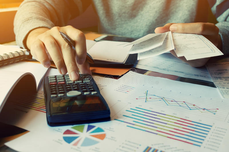 Man calculate invoice and receipt with report summary on desk at royalty free stock photo