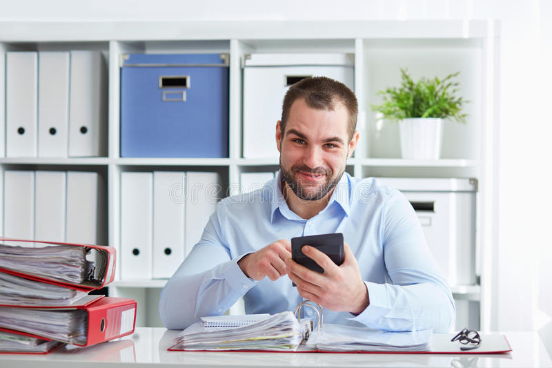 Man calculates taxes. Smiling businessman calculates taxes at desk in office royalty free stock photography