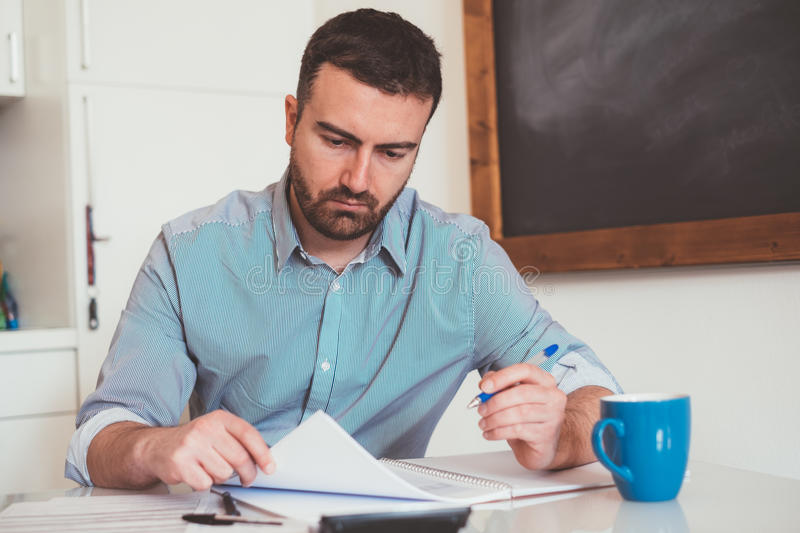 Man calculating bills and tax expense stock photo