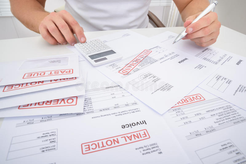 Man calculating unpaid bills stock photography
