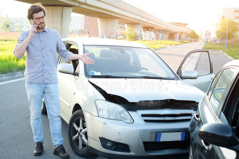 Man calling help after car crash accident on the road royalty free stock image