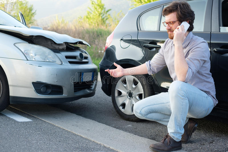 Man calling help after car crash accident on the road stock images
